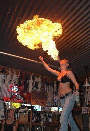 Girl in Jeans und BH spuckt Feuer