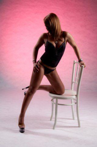 Stripperin hockt auf Stuhl