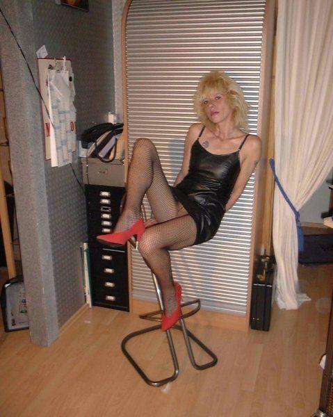 Blonde Schlampe trägt Netzstrumpfhose und rote Heels
