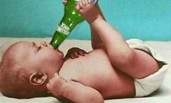 Baby trinkt Flasche Bier mit den Füßen
