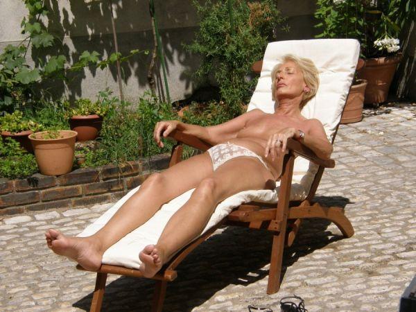 Blonde Granny liegt am Stuhl und sonnt sich