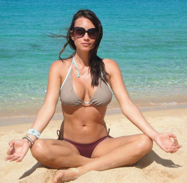 Bikini Schönheit mit großen Brüsten meditiert am Sandstrand